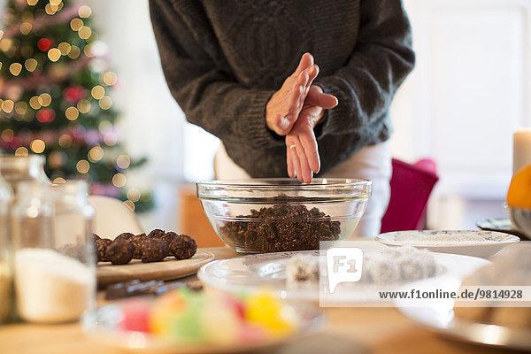 Zubereitung von Weihnachtstrüffeln (Schokolade  Kokosnuss  Hafer) am Küchentisch