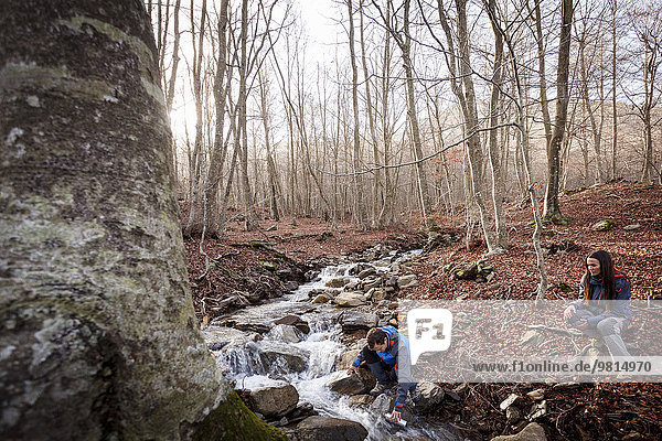 Hikers taking break by stream  Montseny  Barcelona  Catalonia  Spain