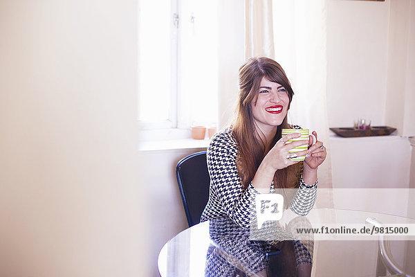Frau am Tisch sitzend  Kaffee trinkend