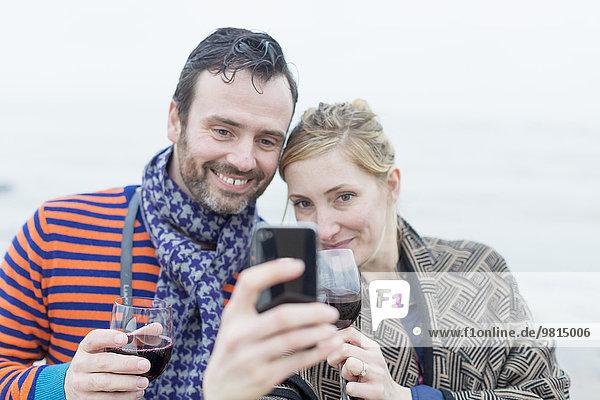 Paar am Strand  Wein trinken  Selbstporträt mit dem Smartphone machen