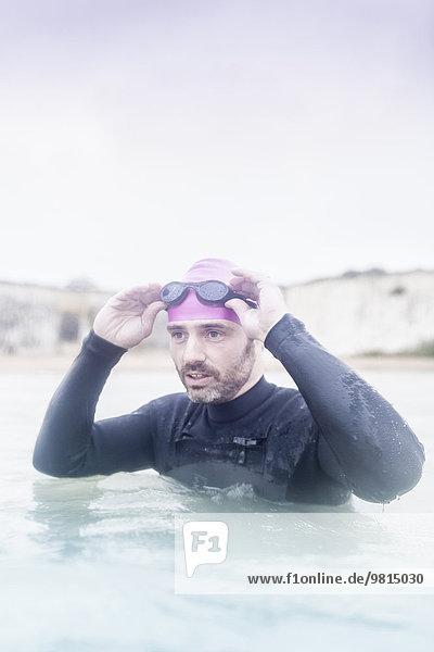 Erwachsener Mann im Meer  im Neoprenanzug  bereit zum Schwimmen