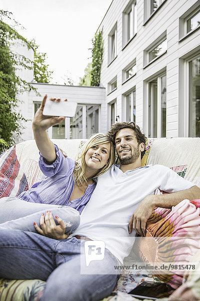 Paar sitzend auf Vintage-Sofa im Garten mit Smartphone Selfie