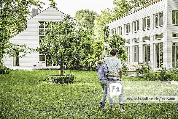 Rückansicht des Paares beim Spaziergang im Garten