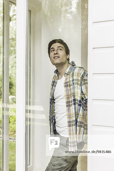 Young man gazing out of window from house