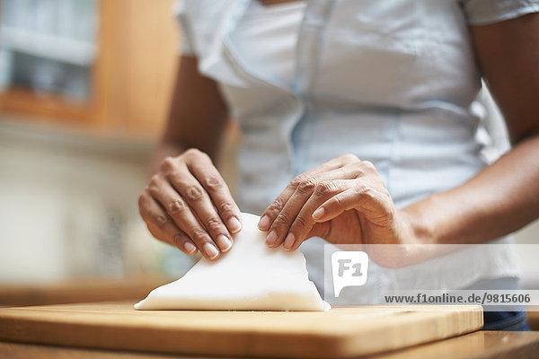 Womans Hände machen Gebäck auf dem Schneidebrett