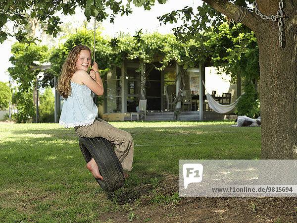 Mädchen schwingt auf Reifenschaukel im Garten