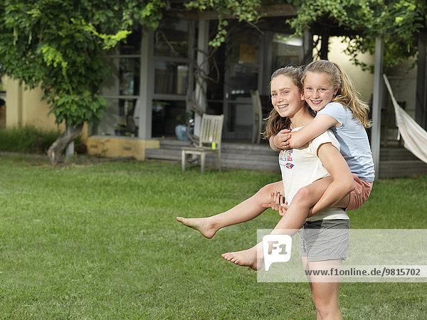 Teenagermädchen beim Huckepackfahren ihrer Schwester im Garten