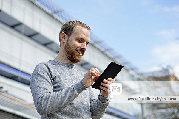 Porträt eines lächelnden jungen Mannes mit Mini-Tablette