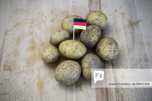 Reihenkartoffeln und kleine deutsche Fahne auf Holz