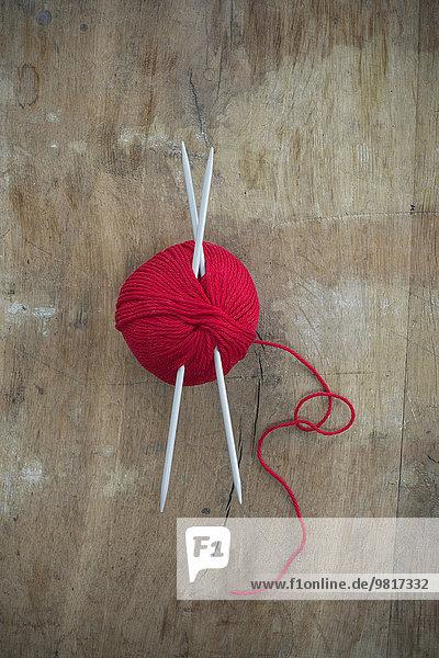 Roter Wollknäuel und Stricknadeln auf Holz