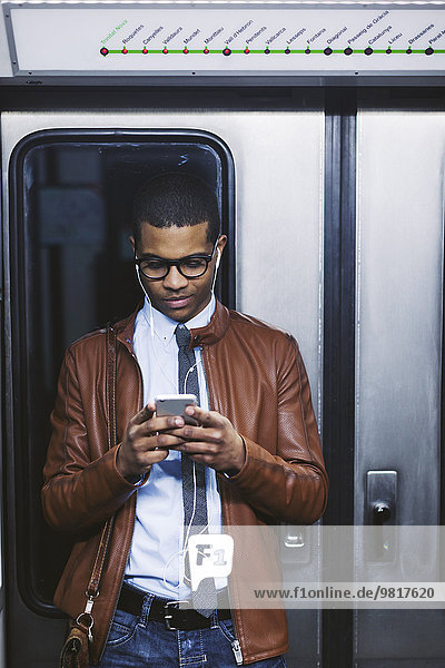 Spanien  Barcelona  Geschäftsmann mit Smartphone und Kopfhörer  der Musik in der U-Bahn hört.