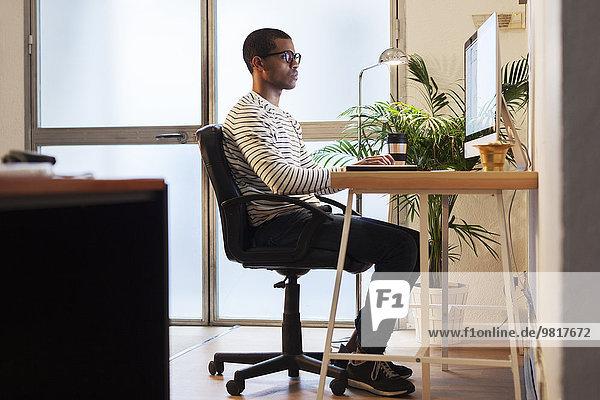 Junger kreativer Mann arbeitet am Computer in seinem Home-Office