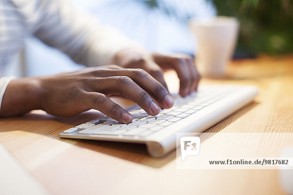 Männerhände beim Tippen auf der Computertastatur