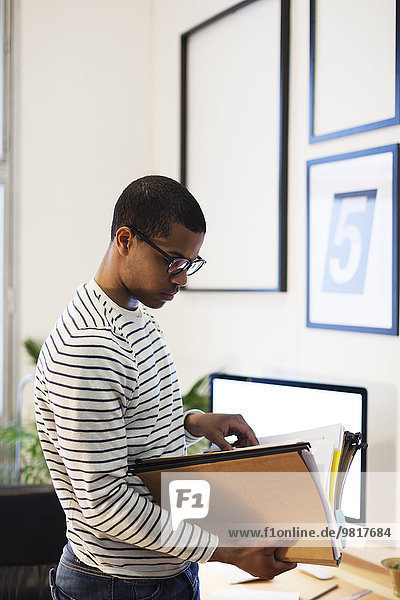 Young creative man with files in his home office
