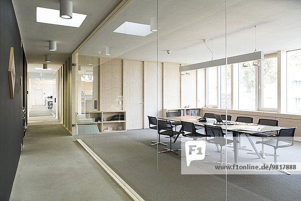 Flur und moderner Konferenzraum durch Glasscheibe getrennt