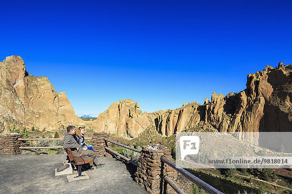 USA  Oregon  Deschutes County  Smith Rock State Park am Crooked River  Touristen auf der Bank am Smith Rock