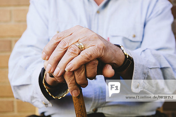 Close-up of old man's hands resting on a cane