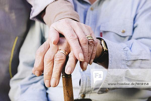 Nahaufnahme der Hände des alten Mannes und der Frau  die auf einem Stock ruhen.