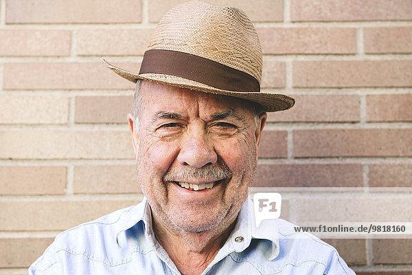 Porträt eines lächelnden alten Mannes mit Strohhut