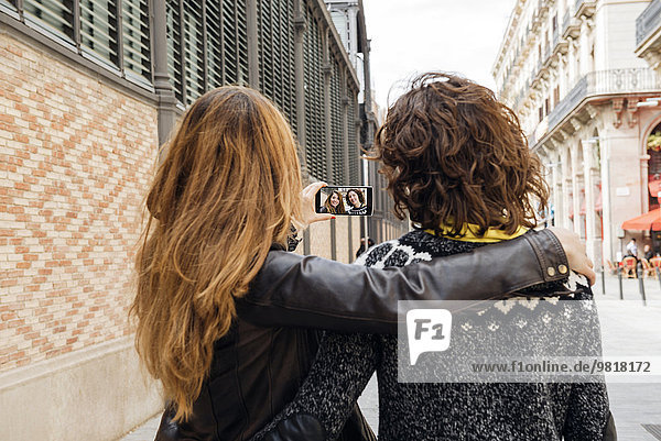Spanien  Barcelona  zwei junge Frauen mit einem Selfie auf der Straße mit Smartphone