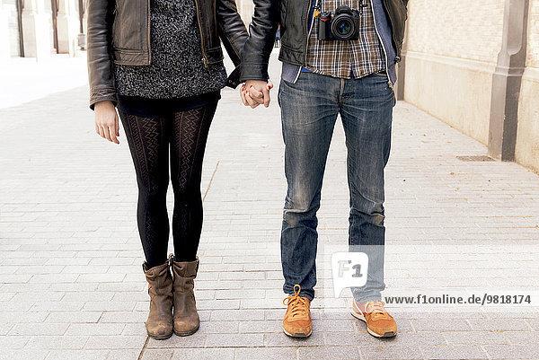 Mann und Frau halten sich auf der Straße an den Händen.