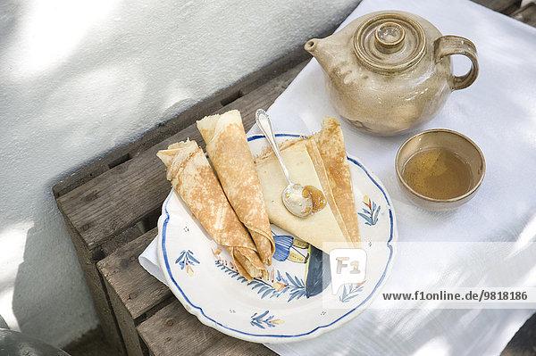 Teller mit Crepes  Tasse Tee und Teekanne