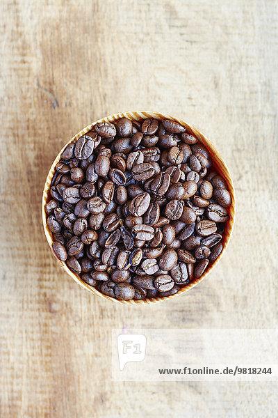 Holzschale mit Kaffeebohnen auf Eichenholz