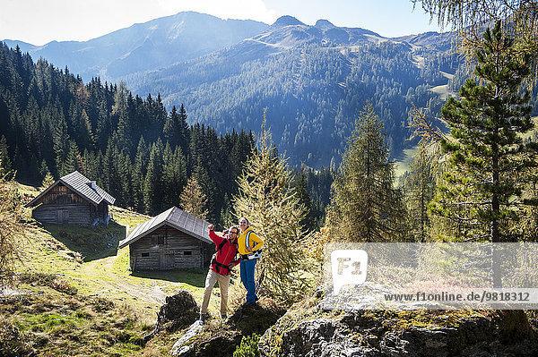Österreich  Altenmarkt-Zauchensee  junges Paar auf einem Felsen stehend mit Blick auf die Umgebung