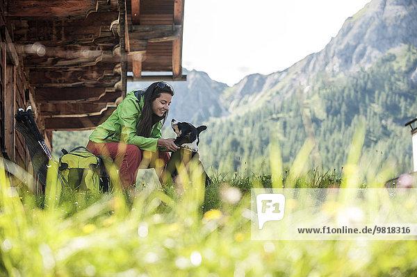 Österreich  Altenmarkt-Zauchensee  junge Frau mit Hund in der Almhütte