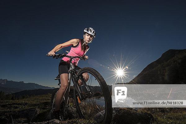 Österreich  Altenmarkt-Zauchensee  junge Frau auf dem Mountainbike bei Sonnenaufgang