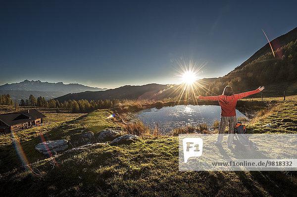 Österreich  Altenmarkt-Zauchensee  junge Frau in den Bergen bei Sonnenaufgang