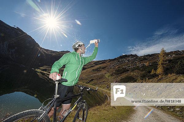 Österreich  Altenmarkt-Zauchensee  junger Mann mit Mountainbike-Kühlung am Bergsee