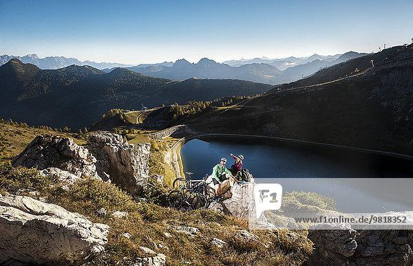 Österreich  Altenmarkt-Zauchensee  junges Paar mit Mountainbikes in den Bergen