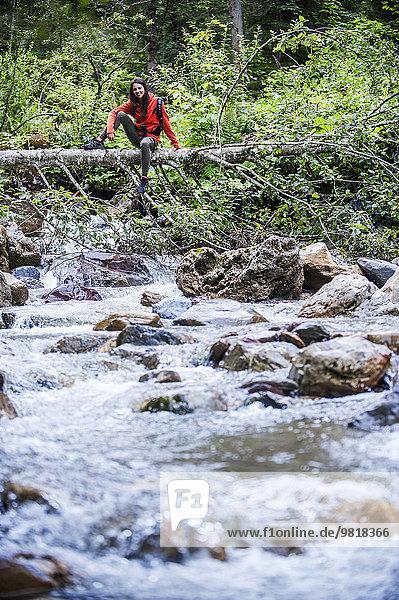 Österreich  Altenmarkt-Zauchensee  junge Wanderin auf Totholz sitzend über einem Fluss