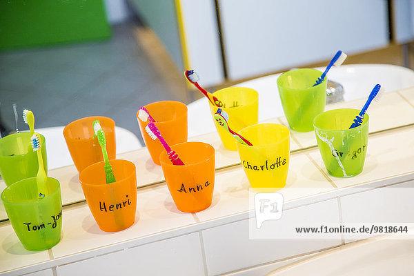 Kunststoffbecher mit Zahnbürsten mit Mähnen von Kindern im Kinderzimmer Kunststoffbecher mit Zahnbürsten mit Mähnen von Kindern im Kinderzimmer
