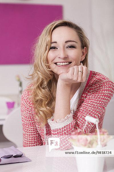 Porträt einer lächelnden blonden Frau in einem Café