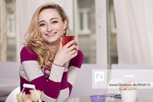 Smiling blond woman sitting in a coffee shop holding drink