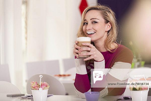 Porträt einer lächelnden blonden Frau mit Milchschnurrbart und einem Glas Latte Macchiato