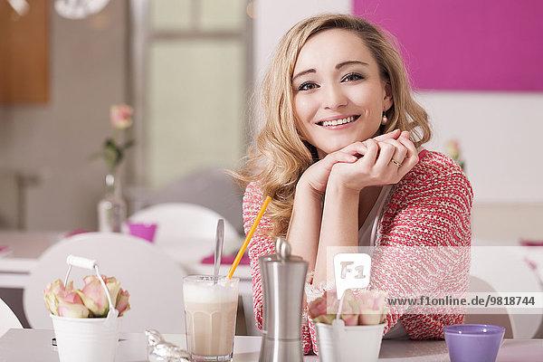 Porträt einer entspannten blonden Frau im Café mit Latte Macciato