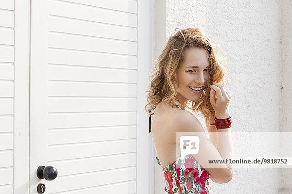 Porträt einer lächelnden jungen Frau mit lockigem Haar