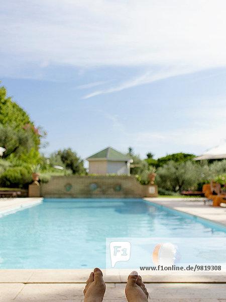 Italien  Toskana  Castiglione della Pescaia  Füße der Frau am Pool sitzend