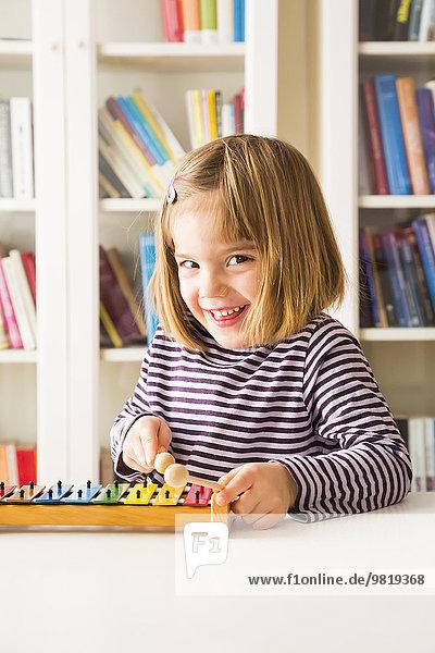 Portrait of happy little girl playing xylophones