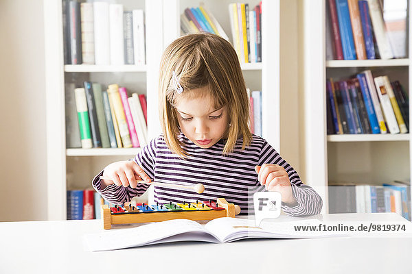 Little girl playing xylophones