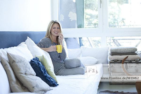 Entspannte Frau auf der Couch sitzend mit einer Tasse Kaffee