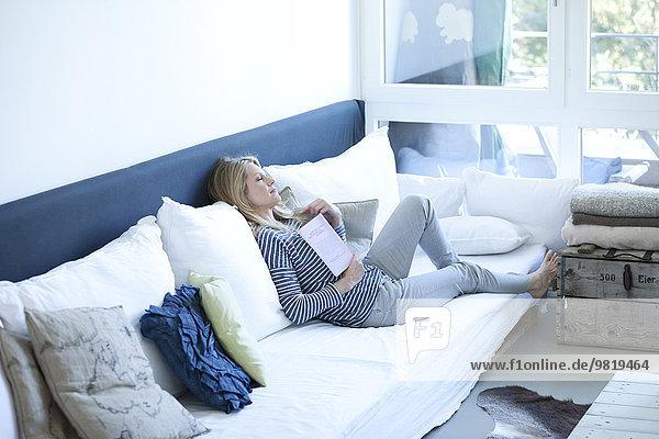 Frau entspannt mit Buch auf der Couch