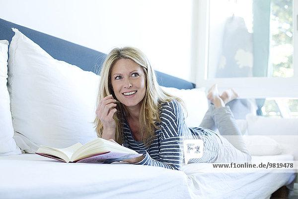 Frau auf der Couch liegend Lesebuch