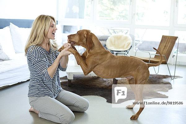 Frau spielt mit ihrem Hund zu Hause