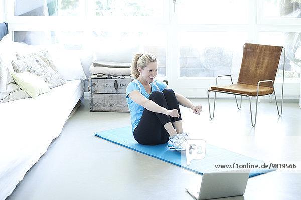 Frau mit Laptop auf Turnmatte im Wohnzimmer
