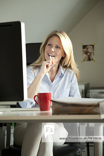 Smiling woman sitting at desk at home