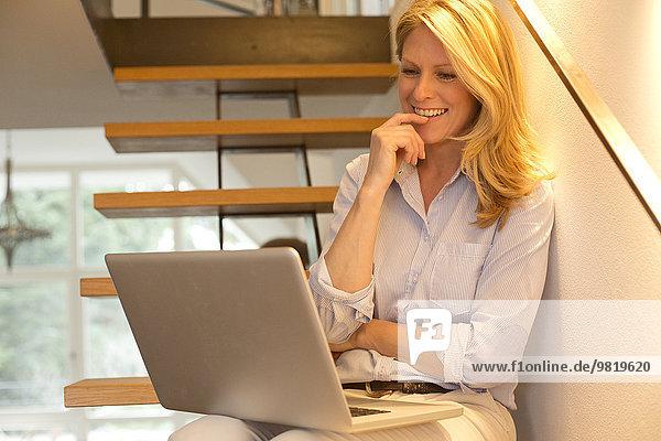 Lächelnde Frau mit Laptop auf der Treppe